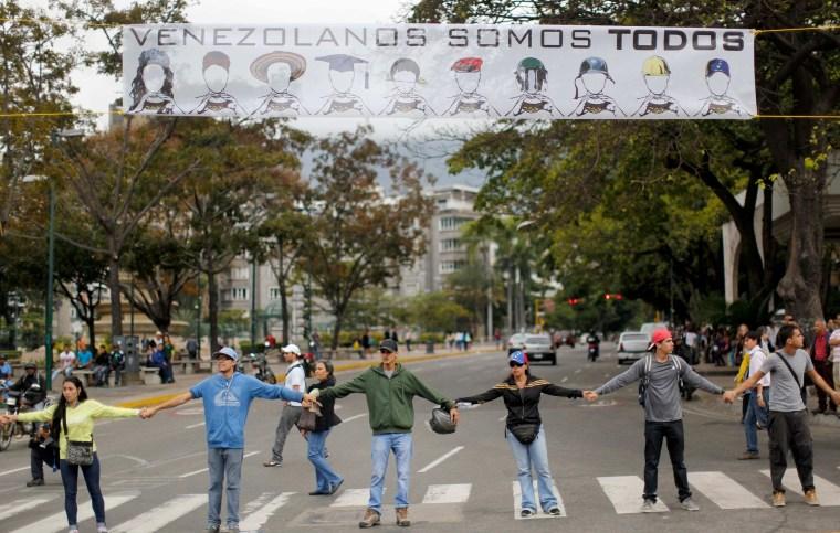 Image: Demonstrators join hands to block the highway at Altamira neighborhood in Caracas