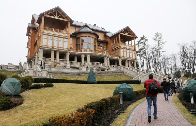 Image: People walk on the territory of Ukrainian President Yanukovych's countryside-residence