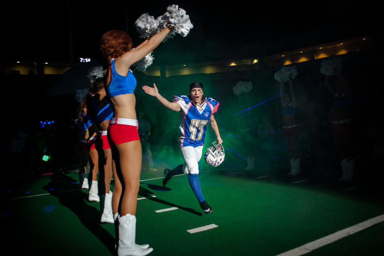 Jennifer Welter, a running back for the Texas Revolution football team, runs onto the field before a game at the Allen Event Center in Allen, Texas, on Feb. 21. Welter, who played in a women's football league for 13 years, is the first woman to play a position other than kicker in men's professional football. The Revolution competes in the Indoor Football League.