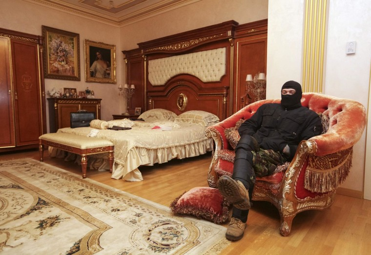 Image: A man sits on a chair in the house of Ukraine's former prosecutor general Pshonka in the village of Gorenichy outside Kiev
