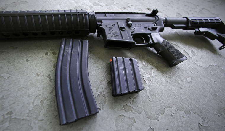 A 30 round magazine, left, and a 10 round magazine, right, rest below an AR-15 rifle.
