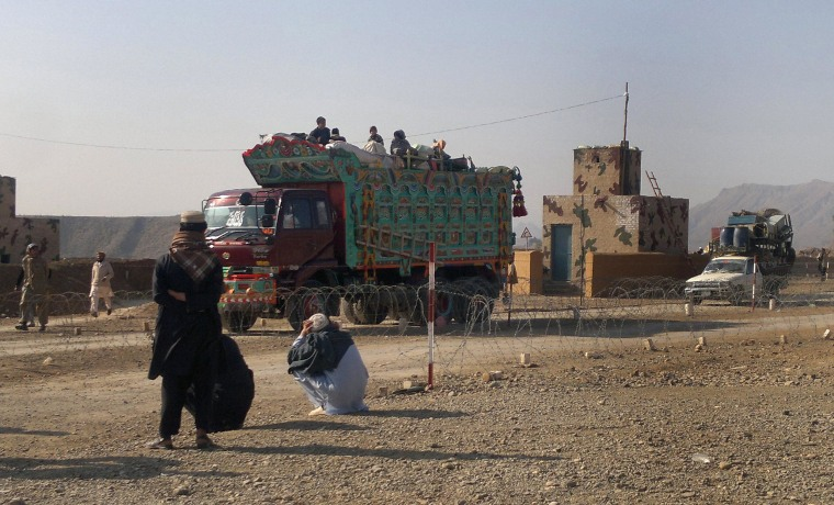 Image: Pakistani tribal families crossing a military check post as they flee after air strikes on Taliban hideouts