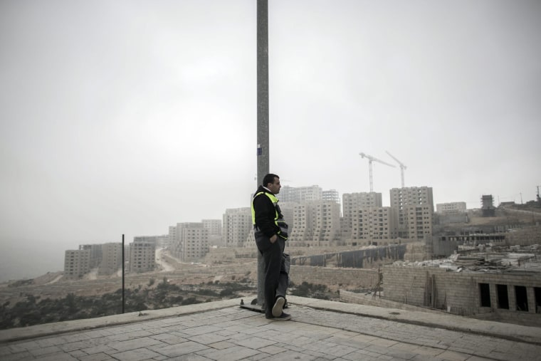 A Palestinian worker leans on a light pole after his shift in Rawabi, West Bank.