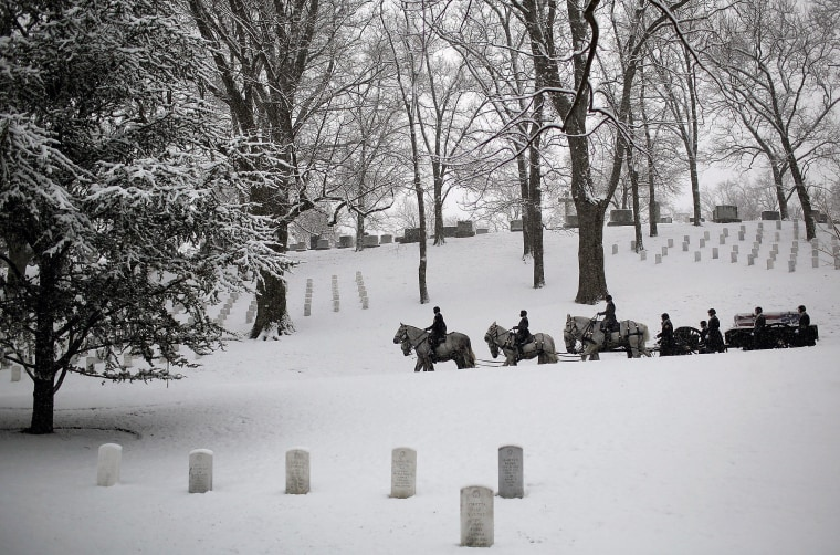 ARLINGTON, VA - FEBRUARY 25:  A burial team leads a horse drawn caisson through a snow covered Arlington National Cemetery on February 25, 2014 in Arlington, Virginia. The Washington DC area received about an inch of snow this morning, adding to an already significant total for the winter.  (Photo by Win McNamee/Getty Images)