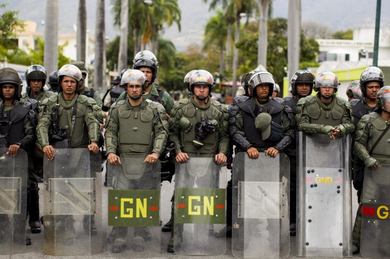Image: Members of the National Bolivarian Guard watch as a group of students and supporters of the political party 'Popular Will' gather at the Alfredo Sadel Square