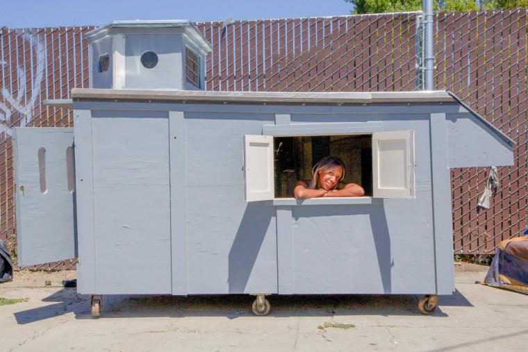 A woman is seen in a shelter built by California artist Gregory Kloehn.