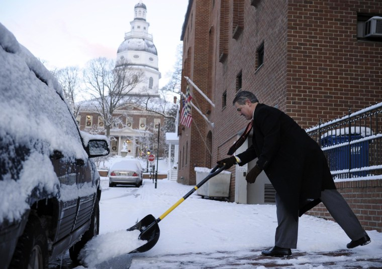Maryland has three of the top five richest neighborhoods in the U.S., a new survey shows. Man shovels snow with the state capitol building in the background.
