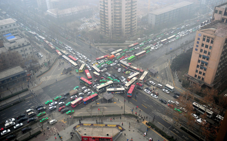 Image:  Vehicles are stuck in a traffic jam in heavy smog after the traffic lights were broken-down