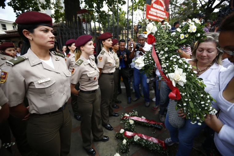 Image: Opposition demonstrators lay flowers with the names of the victims of recent violence at the foot of national guards during a rally in Caracas