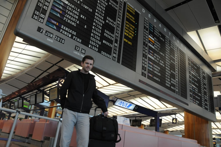 Chris Guillebeau stands in front of a departures board. Travel hacking has helped him travel the world without spending much money.