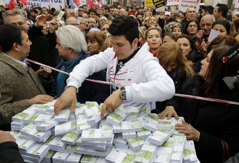 Supporters of Turkey's main opposition Republican People's Party (CHP) stand behind a stack of fake money referring to bribery accusations against the government at a demonstration in Istanbul on Wednesday.