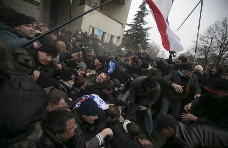 Image: Ukrainian men help pull one another out of a stampede during clashes at rallies held by ethnic Russians and Crimean Tatars in Simferopol
