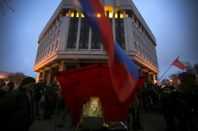 Image: Pro-Russian DJ in traditional clothing looks at her computer during a rally outside the Crimean parliament building in Simferopol