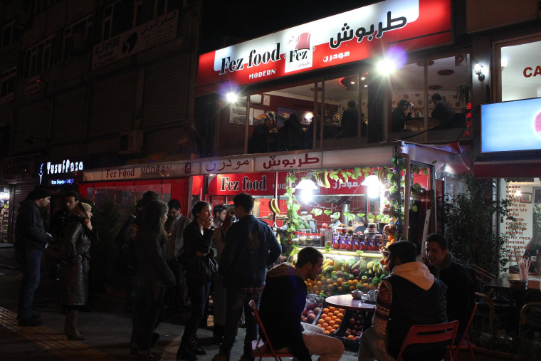 People congregate in front of a location of the fast food chain Fez founded by Syrian Mohamad Nizar Bitar, Jan. 19, 2014 in Istanbul.