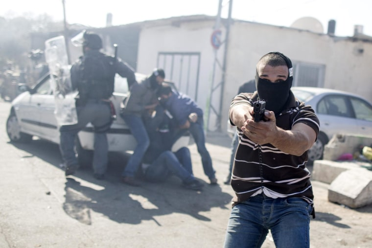 Image: Image:  An Israeli undercover policeman point his gun (R) while other officers arrest a Palestinian stone thrower during clashes following Friday prayers at the east Jerusalem neighbourhood of Ras Al Amude