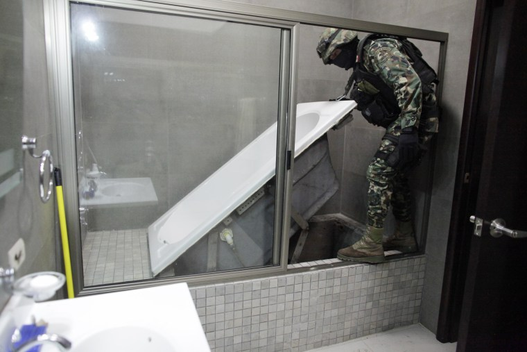 "A Mexican marine lifts a bathtub that leads to a tunnel and exits in the city's drainage system at one of the houses of Joaquin ""Chapo"" Guzman in Culiacan February 27, 2014."