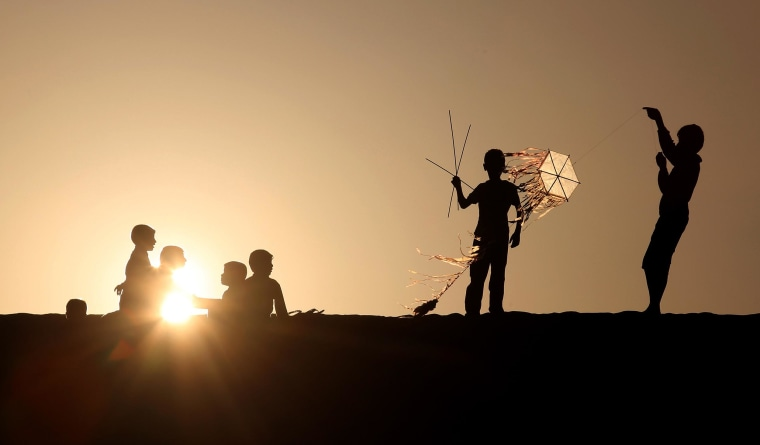 Palestinian children fly kites and sit watching the sunset in Khan Younis, a town and refugee camp in the southern Gaza Strip, on Feb. 28, 2014.