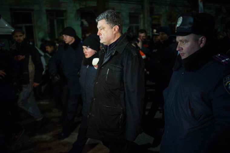 Ukrainian MP Petro Poroshenko is accompanied by police as he is trailed by pro-Russian demonstrators in the Crimean city of Simferopol on Feb. 28, 2014.