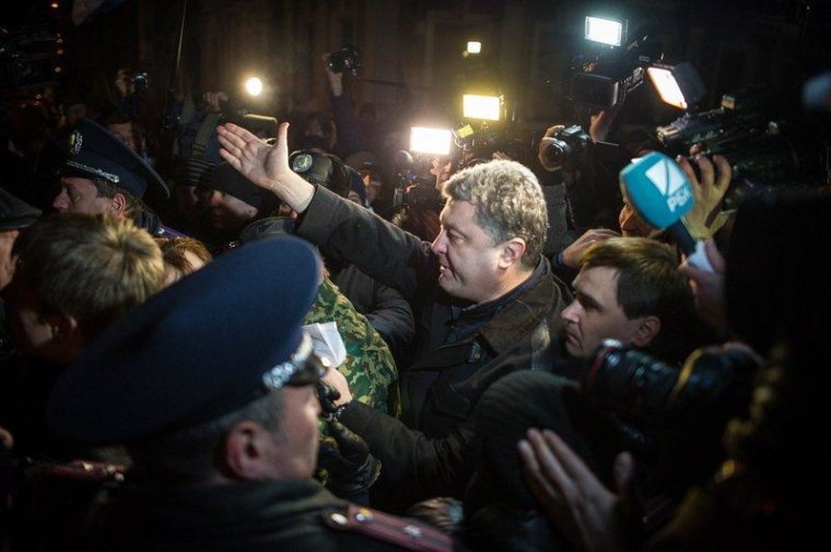 A crowd of angry pro-Russian demonstrators, as well as police and media, accompany Ukrainian MP Petro Poroshenko as he walks through the streets of the Crimean city of Simferopol.