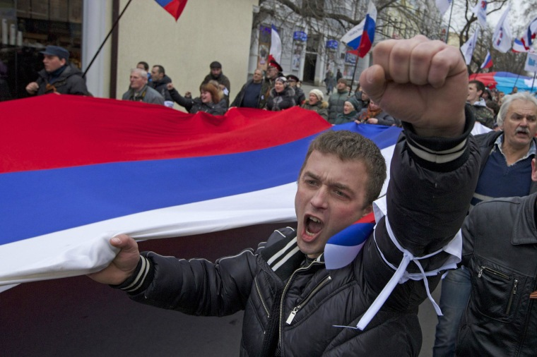 Image: Local residents carry Russian flags as they rally in the streets of Crimean capital of Simferopol on Saturday.