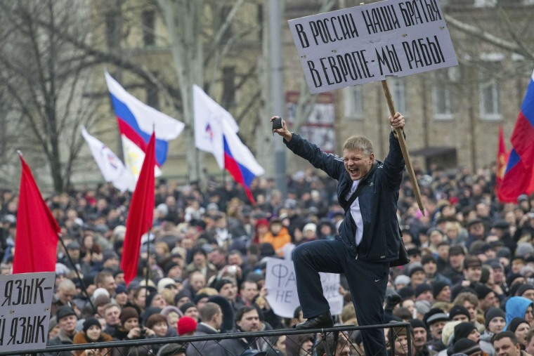 "Pro-Russian protesters with Russian flags take part in a rally in central Donetsk in eastern Ukraine on Saturday. The banner reads, ""In Russia, we have brothers, In Europe, we are slaves."""