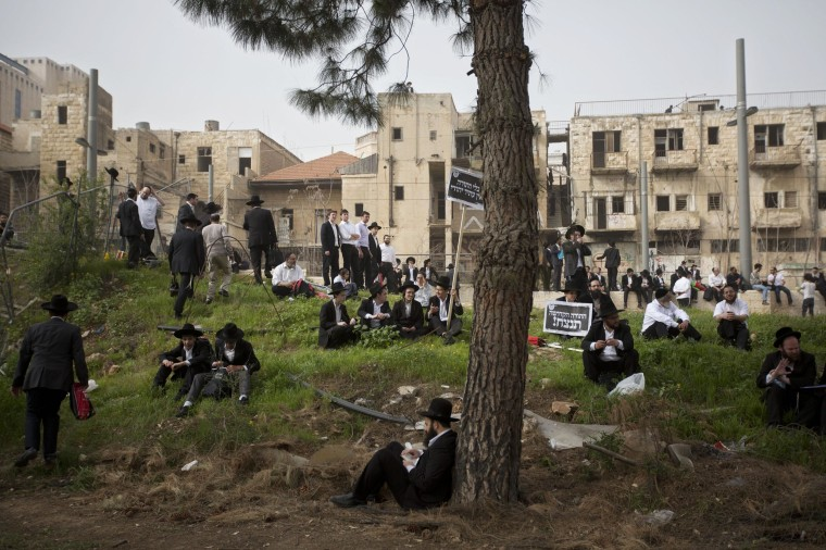 Image: Ultra-Orthodox Jewish men sit during a rally in Jerusalem