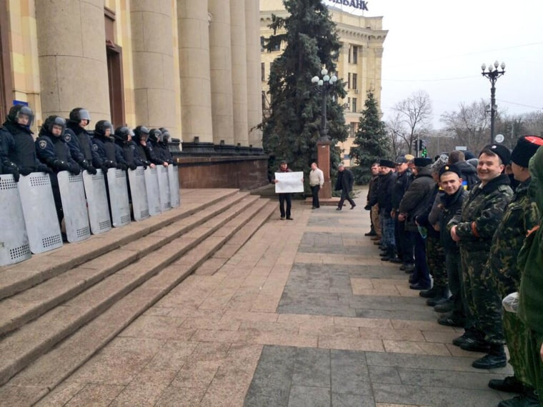 Pro-Russian protestors from the Cossack community face riot police outside the administrative building in Kharkiv