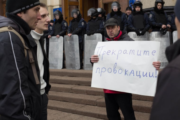 A man holding a sign that reads 'Stop the provocations' during a standoff outside a government building in Kharkiv on Monday. He told NBC News the message was aimed at both sides.