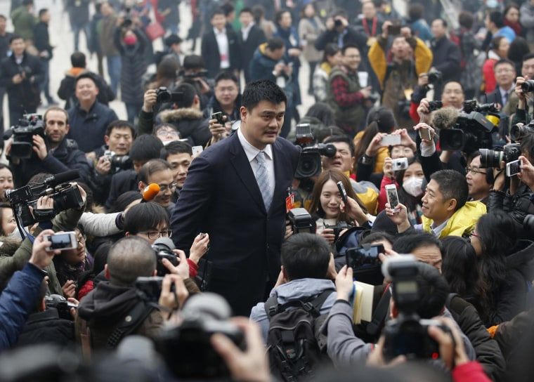 Image: Former NBA basketball player Yao is surrounded by media