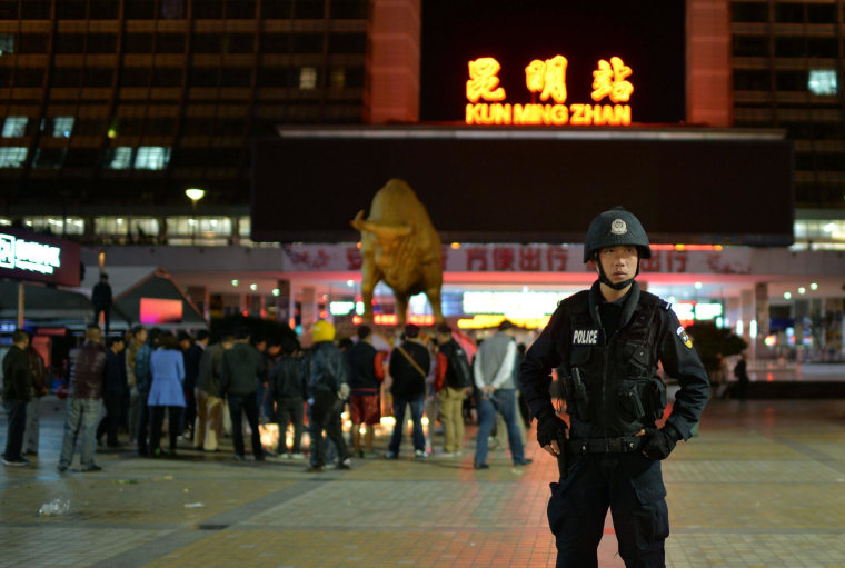 Image: A policeman on guard as mourners light candles at the scene of an attack at the train station in Kunming, southwestern China