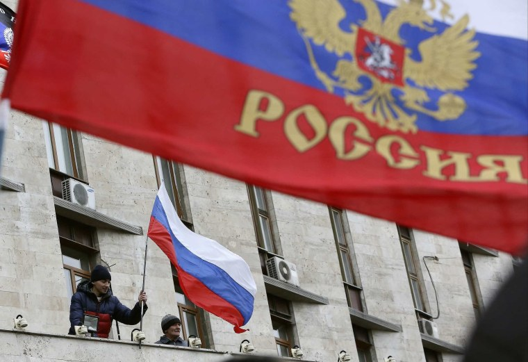 Image: Pro-Russian demonstrators erect a Russian flag outside the regional government building in Donetsk