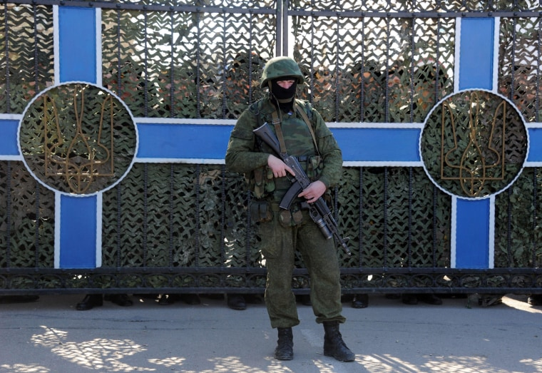 Image: Ukrainian soldier stands behind a fence while unidentified armed men block the headquarters of the Ukrainian Navy