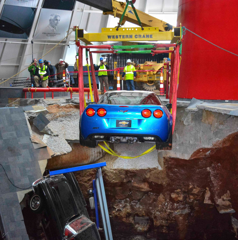 """Image: Workers use a crane to recover the 2009 Corvette ZR-1 """"Blue Devil,"""" from the sinkhole at the National Corvette Museum in Kentucky"""