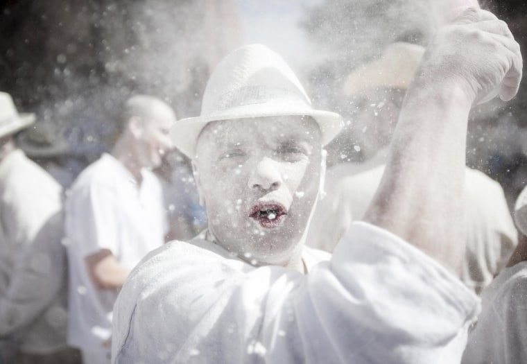 Image:  Revelers known as 'Los Indianos,' throw talcum powder over each other during carnival