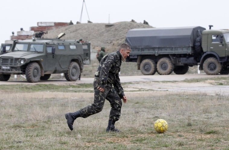 Image: A Ukrainian serviceman kicks a soccer ball near Russian military vehicles at the Belbek air base in the Crimea region