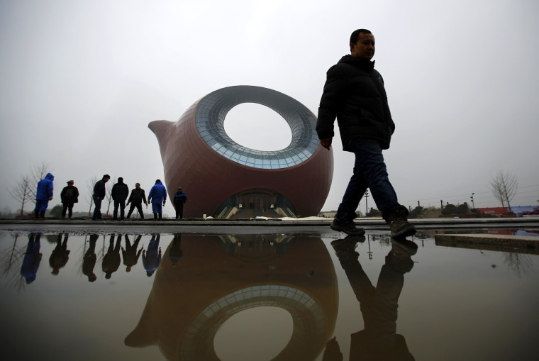 Image: Workers stand next to a building shaped like a clay teapot in Wuxi
