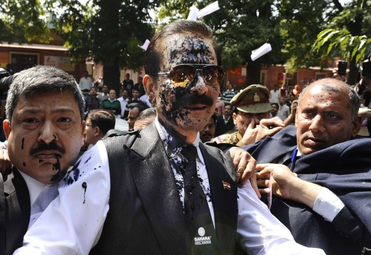 Image: Chairman of Sahara India Pariwar Subrata Roy, his face smeared with ink thrown by a lawyer, walks into the Supreme Court in New Delhi