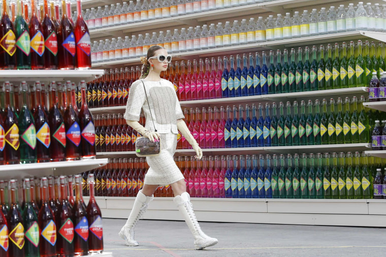 """Image: A model presents a creation by German designer Karl Lagerfeld as part of his Fall/Winter 2014-2015 women's ready-to-wear collection for French fashion house Chanel at the Grand Palais transformed into a """"Chanel Shopping Center"""" during Paris Fashion"""