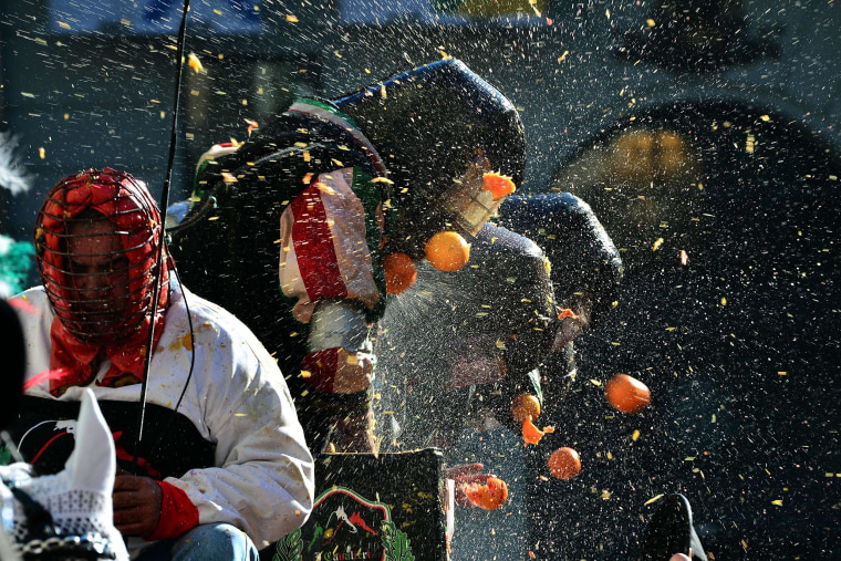 """Men with helmets are hit by oranges during the traditional """"battle of the oranges"""" held during the carnival in Ivrea, near Turin, on Tuesday. During the event which marks the people's rebellion against tyrannical lords who ruled the town in the Middle Ages, revelers parading on floats represent guards of the tyrant, while those on foot act as townsfolk."""