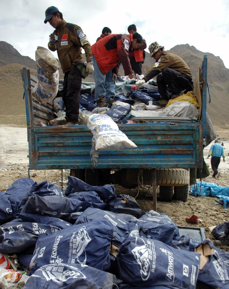 Chinese environmental activists dump garbage bags at a garbage processing centre in Lhasa, Tibet.