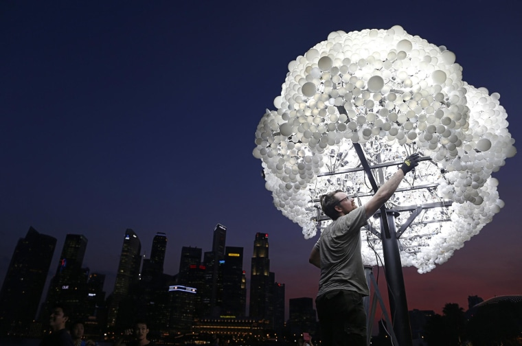 """Image: Wayne Garrett of Canada makes final touches to his art installation """"CLOUD"""" ,made up of 5000 new and recycled lightbulbs, along the Marina Bay in Singapore"""