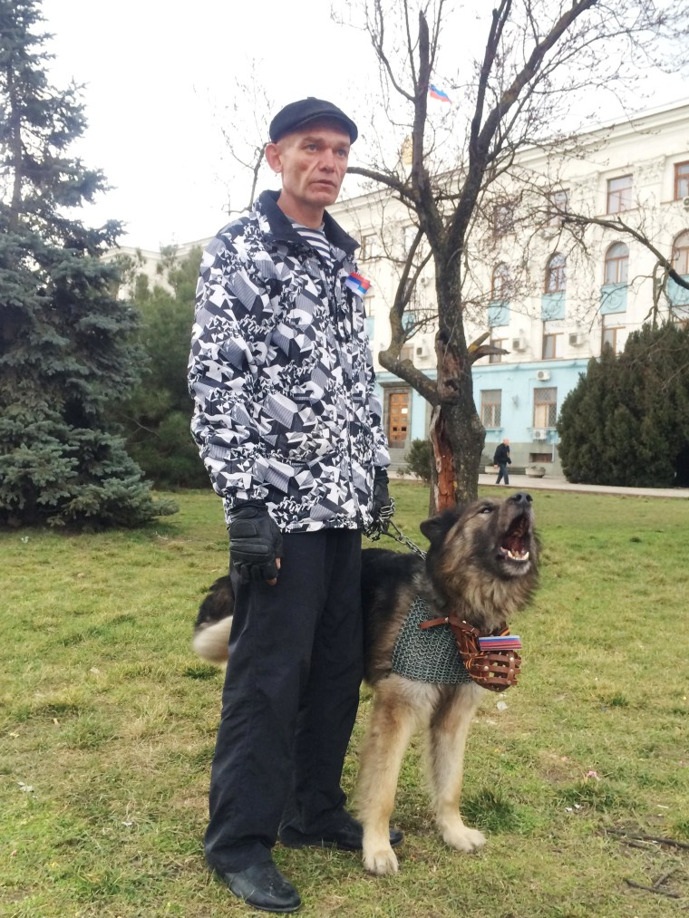 """Alexandr Gerasimov, a member of one of the Crimean self-defense units in Simferopol. He is with his chainmail wearing German shepherd, """"Flint,"""" a former army dog given to him as a gift by another Ukrainian border guard."""