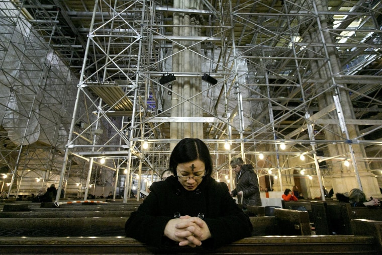 Image: A woman prays at St. Patrick's Cathedral