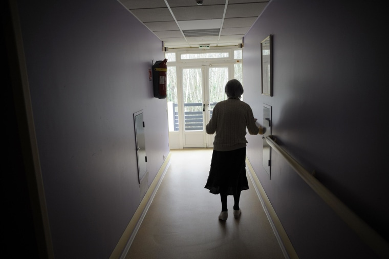 A woman, suffering from Alzheimer's desease, walks in a corridor on March 18, 2011 in a retirement house in Angervilliers, eastern France.