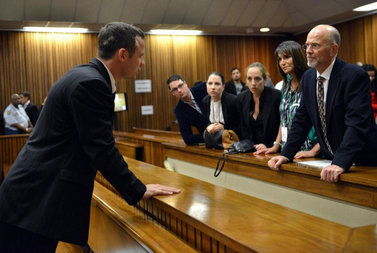 Image: Oscar Pistorius chats with family members during a break in court proceedings