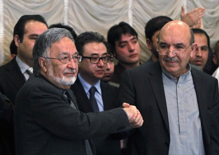 Afghan presidential candidate Qayum Karzai, right, shakes hand with fellow presidential candidate Zalmai Rassoul, left, during a news conference in Kabul on March 6, 2014.
