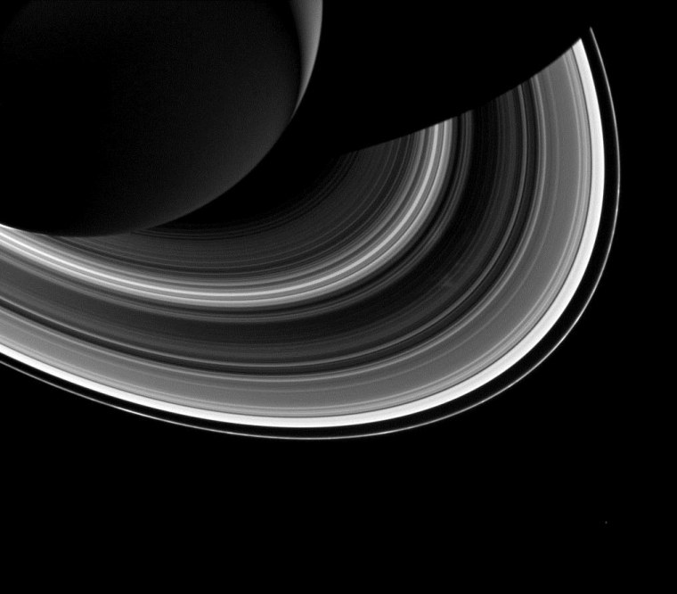 Among the interplay of Saturn's shadow and rings, Mimas, which appears in the lower-right corner of the image, orbits Saturn as a set of the ever-intriguing spokes appear in the B ring (just to the right of center).