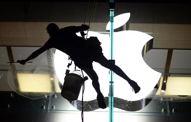Image: Worker cleans glass panels of Apple store in Sydney, Australia