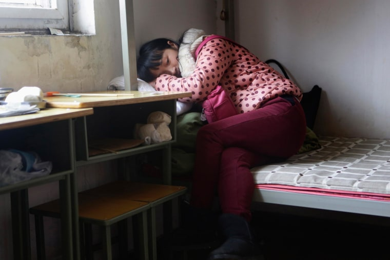 Image: Wang Feng rests on a bed before she leaves for work, at Huaxia Liangtse Massage Training Centre in Zhengzhou, Henan province