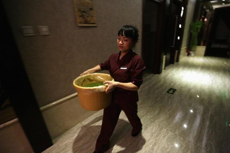 Image: Wang Feng carries a bucket of water at Huaxia Liangtse Wangjing store, in Beijing